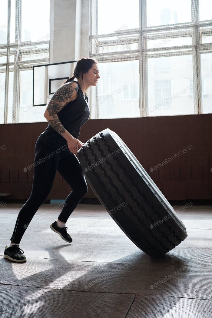 sportliche tätowierte Frau in schwarzer Activewear Aufbaumuskulatur durch Flipping Reifen