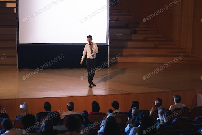 Businessman standing and giving presentation in auditorium in auditorium