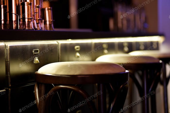 Bar counter with high chairs in empty cozy restaurant