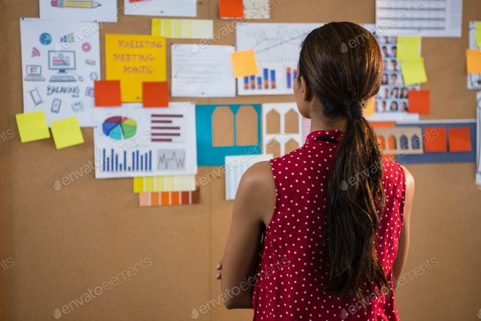 Female executive looking at the bulletin board in office
