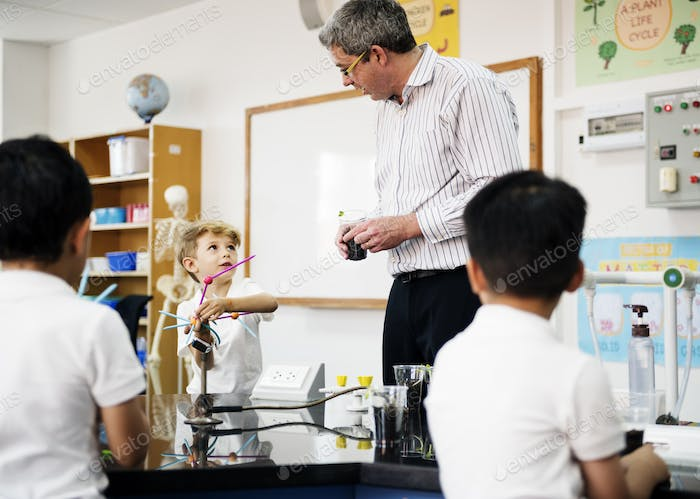 Group of diverse kindergarten students learning experiment in sc