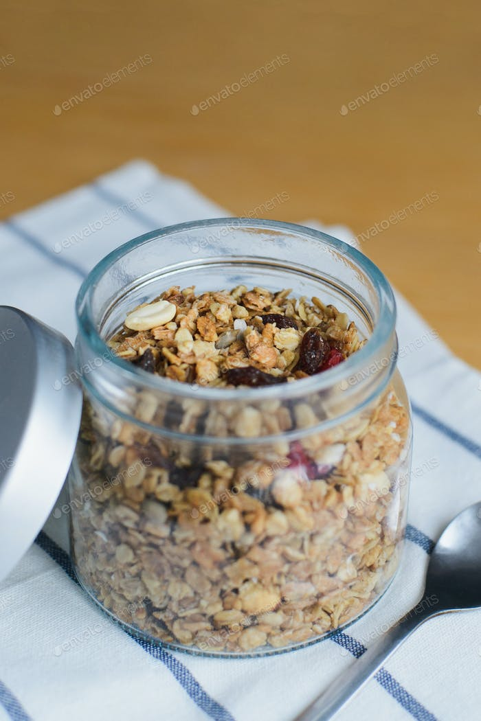 granola with peanuts, hazelnuts, oat and wheat flakes in glass bowl