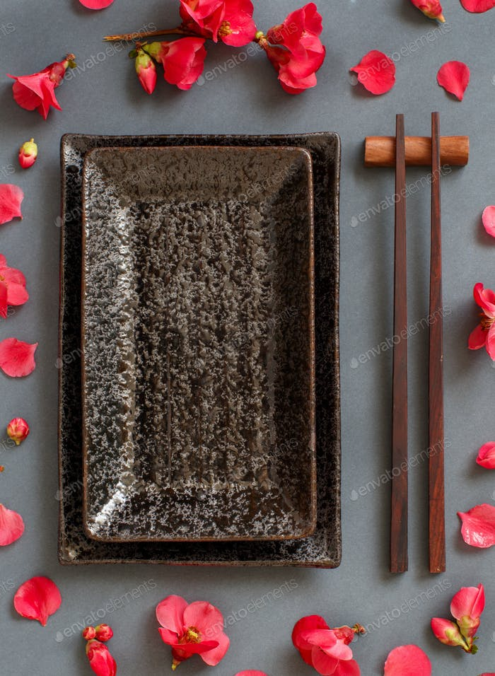 Chopsticks, rectangular plate and pink flowers on gray background