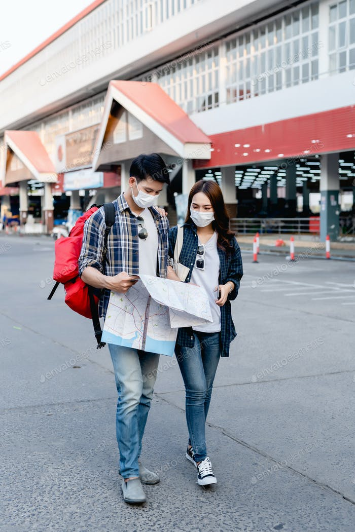 Young backpacker couple in mask checking location on paper map