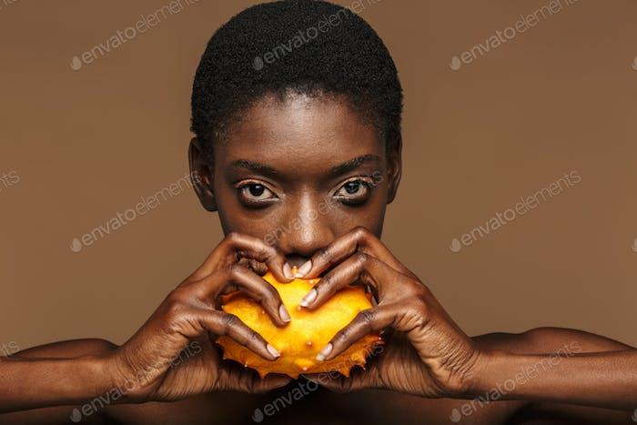 Schönheit Porträt von halbnackte afrikanische Frau hält Kiwano gehörnte Melone