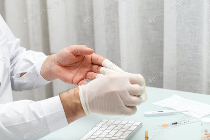 Doctor taking off the gloves