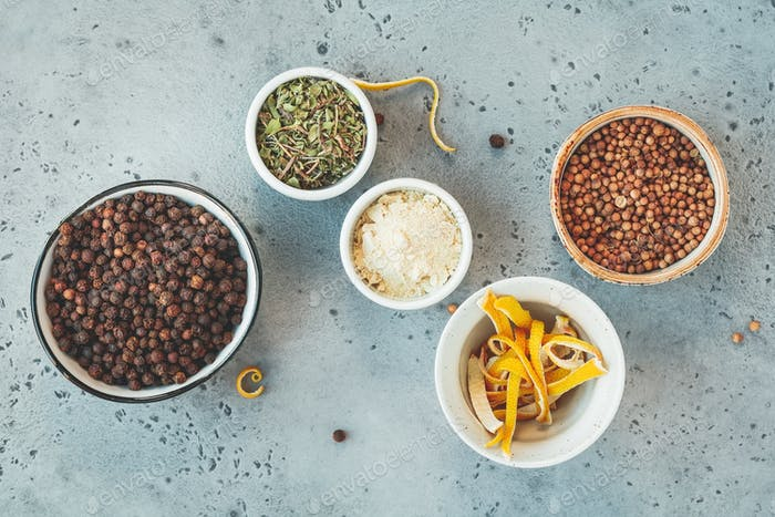 Various spices in bowls on a grey textured background. Top view.