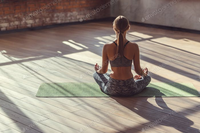 Young woman in lotus pose indoors