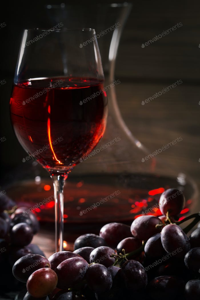 Glass of red wine and a bunch of grapes