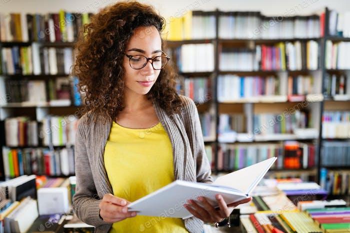 Bildung, Gymnasium, Universität, Lernen und Menschen Konzept. Lächelnd Student Mädchen Buch lesen