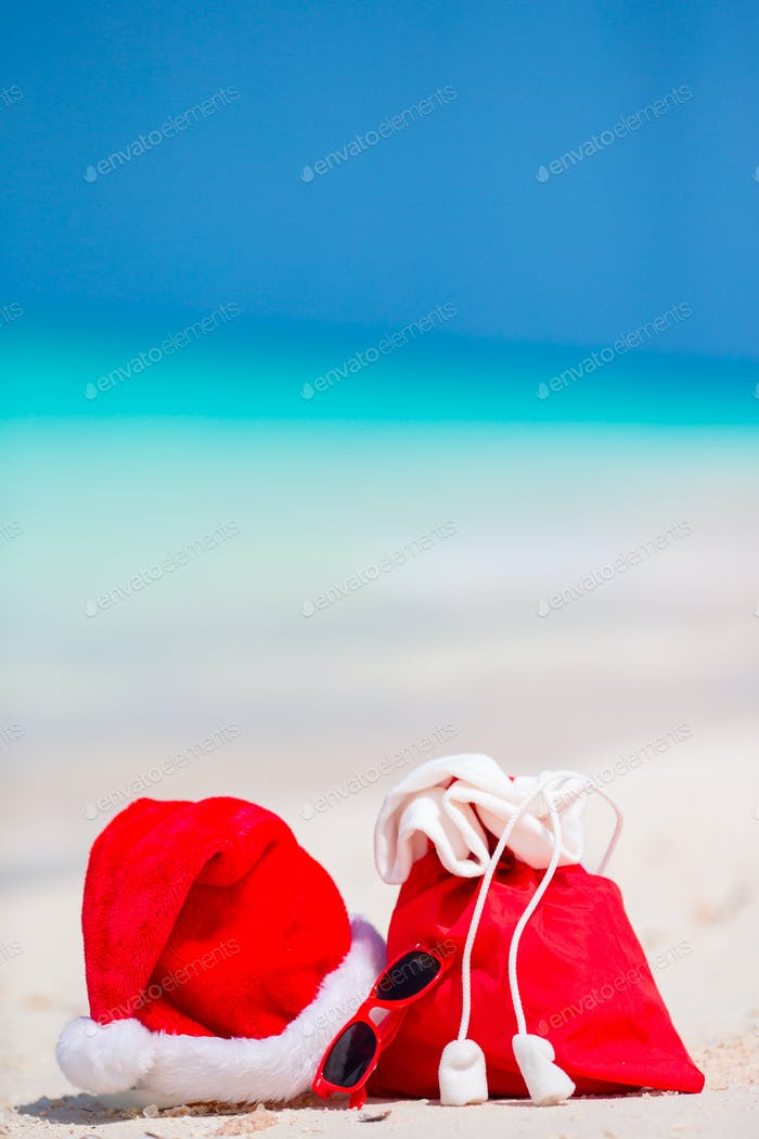 Closeup of red Santa bag and Santa Claus hat on beach. Xmas travel vacation and travel cuprise