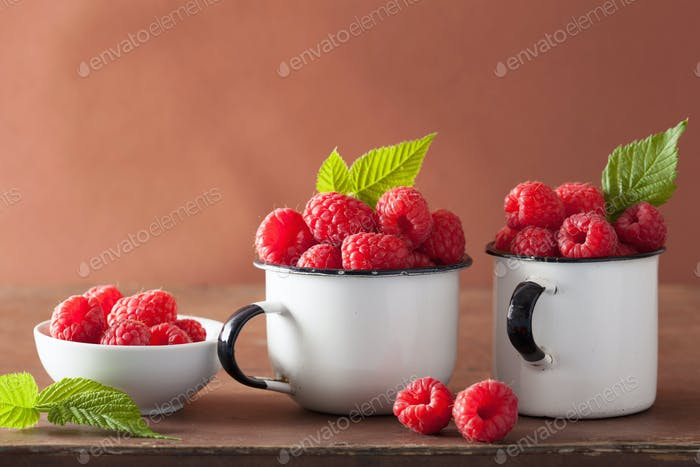 fresh raspberry in enamel cups over wooden background