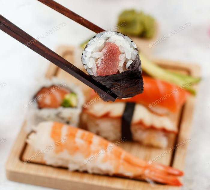 Close up of hand taking roll with chopsticks from a plate