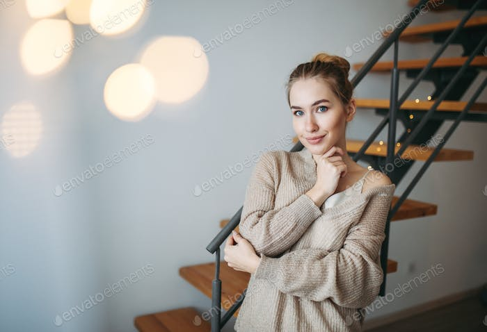 Beautiful girl in evening beige silk dress and cozy cardigan in front of stairs at home