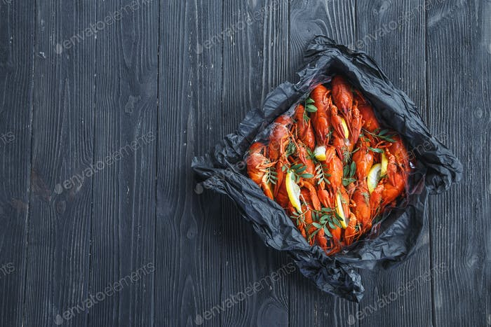 Top view of box with boiled crawfish on rustic wooden background