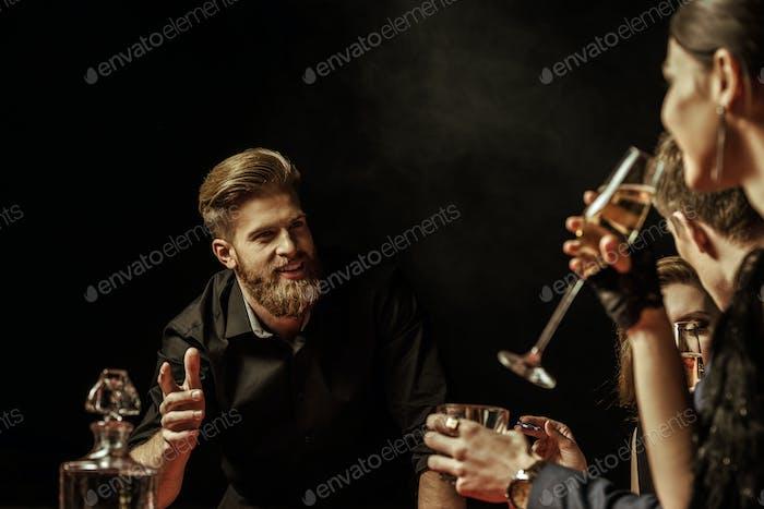 Jóvenes felices bebiendo bebidas alcohólicas y hablando en negro