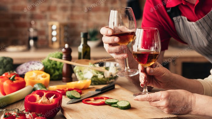Loving seniors clinking glasses with wine at kitchen