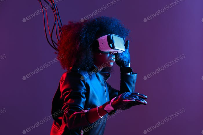 Mod curly dark haired girl dressed in black leather jacket and gloves uses the virtual reality