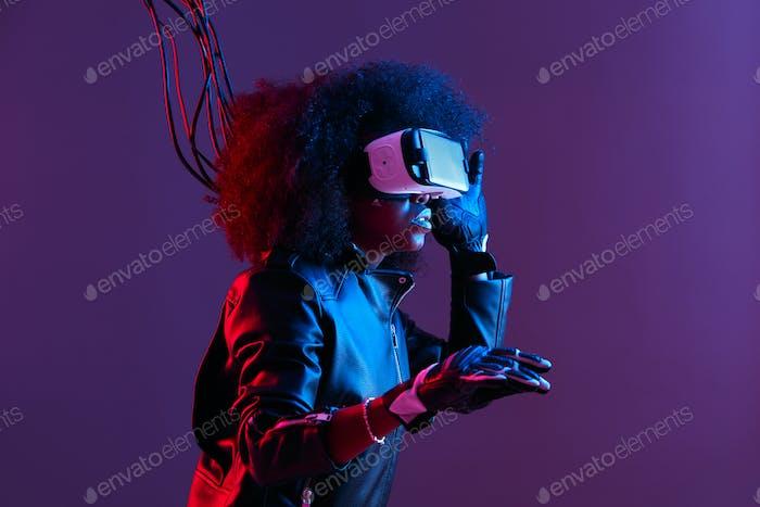 Mod lockig dunkelhaarige Mädchen in schwarzen Lederjacke und Handschuhe gekleidet verwendet die virtuelle Realität