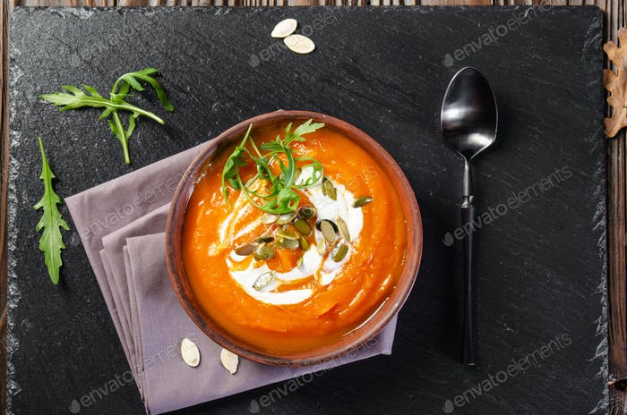 Flat lay view at tasty homemade rustic pumpkin soup with seeds in clay dish on slate tray