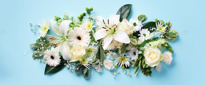 Spring composition of white flowers on blue paper background with copy space. Creative layout. Flat