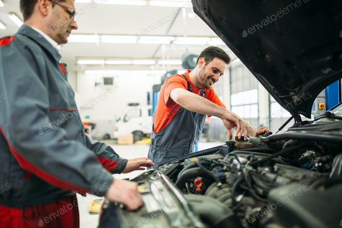 Car mechanics working at automotive service center