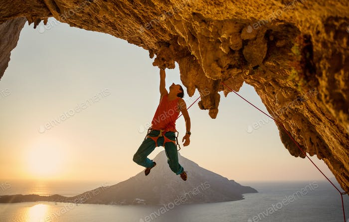 Male rock climber hanging with one hand on challenging route on cliff