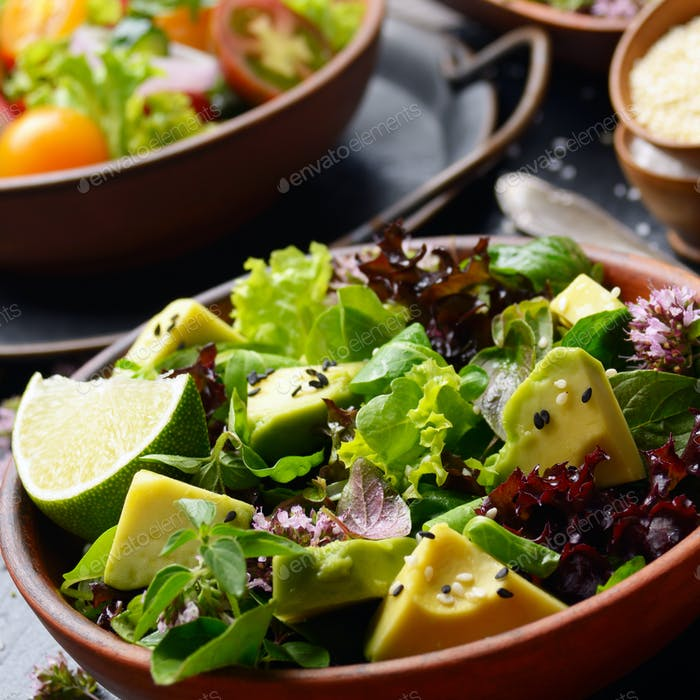 Clay dish with salad of avocado, green and violet lettuce, lamb'