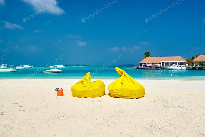 Tropical beach with yellow beanbag chairs