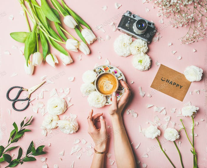 Female hands holding coffee, flowers, film camera and sign happy