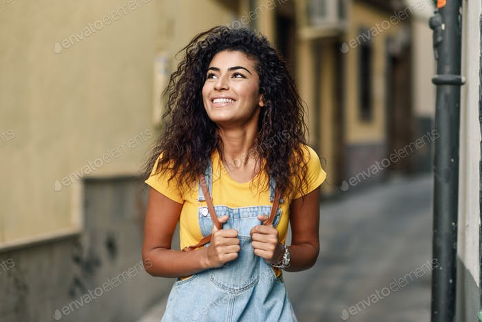 Young North African woman with black curly hairstyle outdoors.