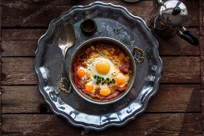 Turkish basturma with fried egg in a copper pan, rustic style