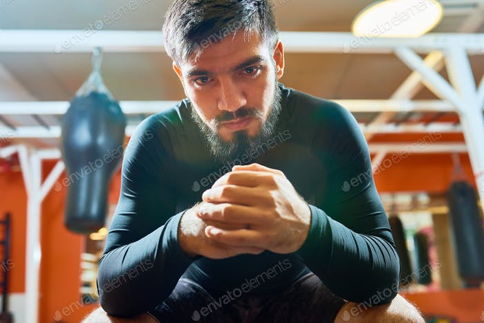 Brutal bearded sportsman in boxing gym