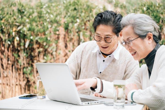 Старшая пара с помощью ноутбука во дворе