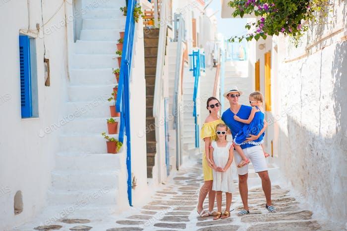 Familienurlaub in der kleinen alten griechischen Stadt. Eltern und Kinder auf der Straße des griechischen traditionellen Dorfes auf