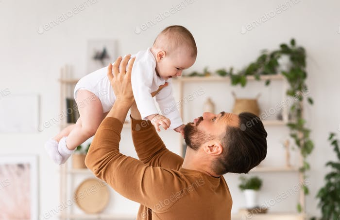 Cute Daddy Playing With Newborn Baby Daughter Standing At Home