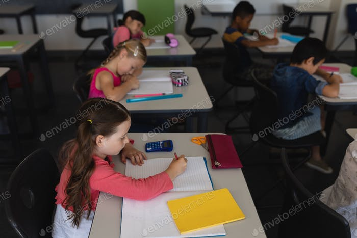 Side view of kids studying and sitting at desk in classroom  in school