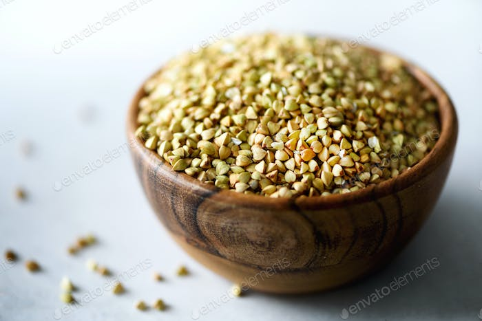 Raw organic green buckwheat in wooden bowl and rosemary on grey background. Copy space. Food