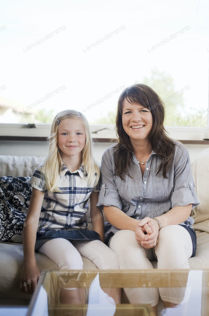 Portrait of happy mother and daughter sitting on sofa at home