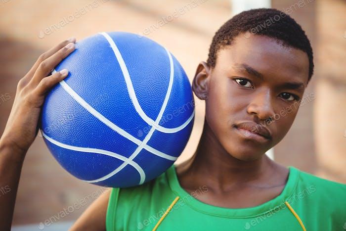 Portrait of teenage boy with basketball on shoulder