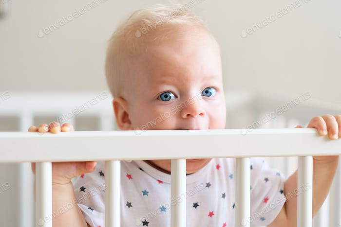 Baby boy standing in crib