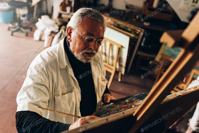 Alter Mann Künstler Malerei Öle in seinem Atelier.