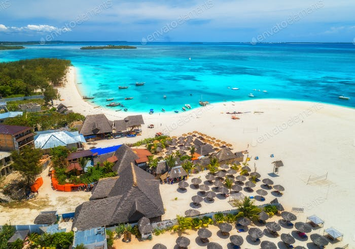 Aerial view of tropical sandy beach with palms and umbrellas, sea