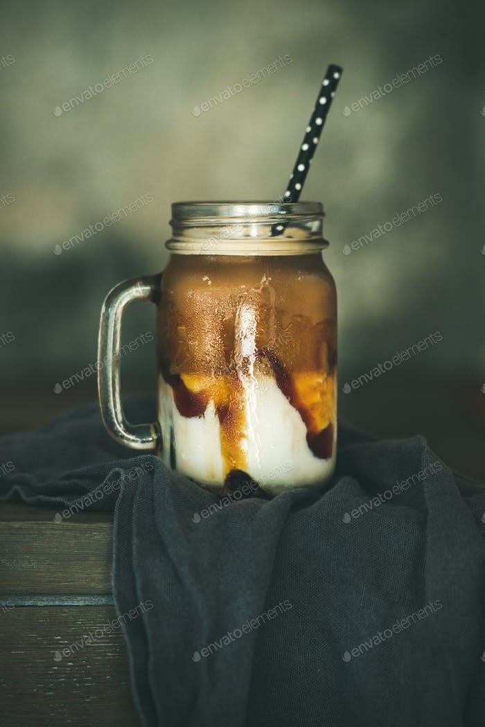 Iced caramel macciato coffee with milk in jar