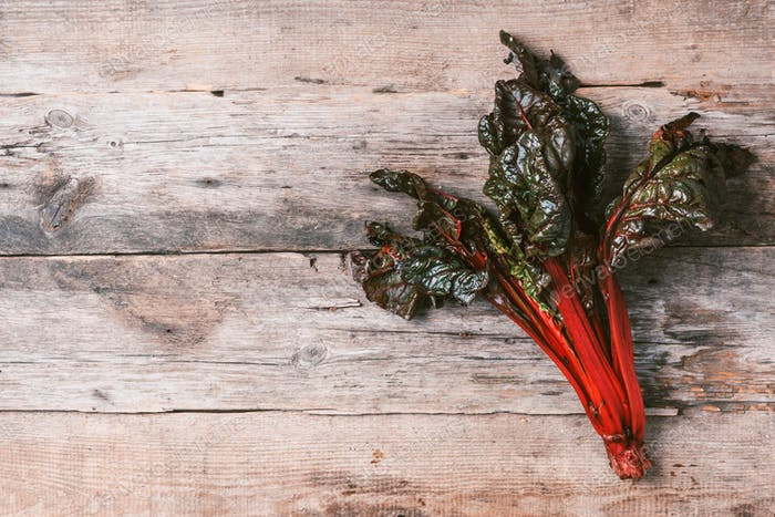 Multi-colored swiss chard on wooden background. Top view. Copy space. Zero waste, organic vegetables