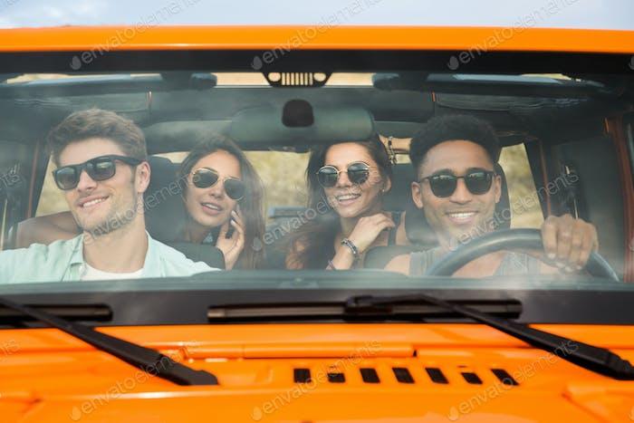 Gruppe von vier fröhlichen jungen Freunden sitzen in einem Auto