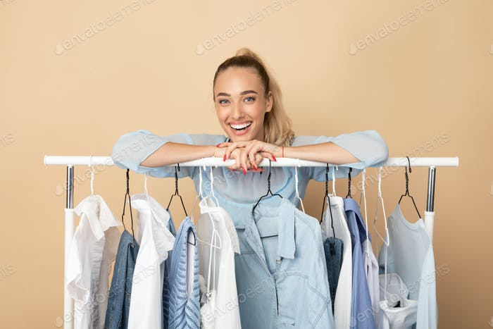 Portrait of cheerful woman standing near rack with cloth