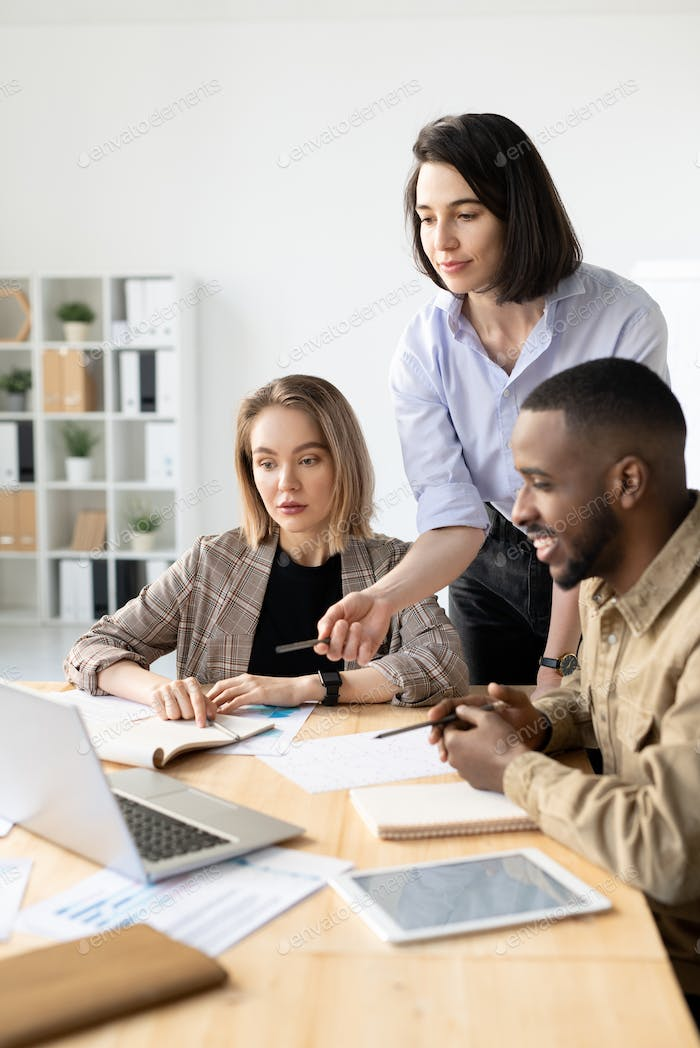 Two young businesswomen and their foreign colleague sitting in front of laptop
