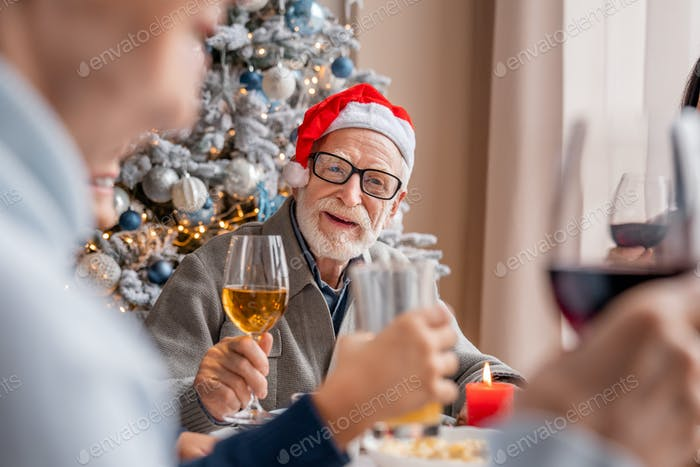 Senior smiling man enjoying christmas dinner together at home with his family toasting