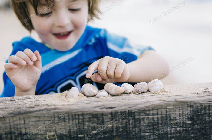 A boy at the beach counting shells lined up on a breakwater.